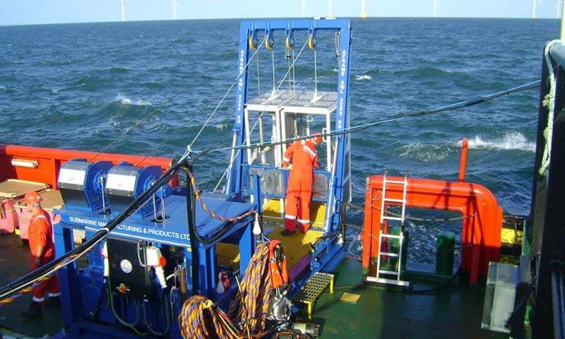 Diving cage being launches into the sea
