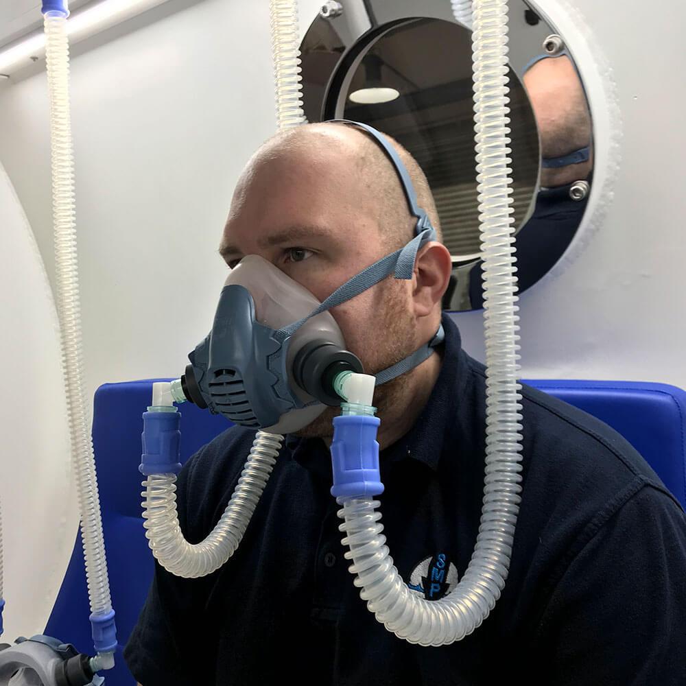 man wearing oxygen mask inside hyperbaric chamber